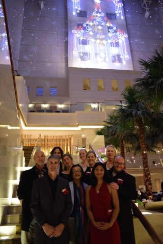 Group photo in front of Christmas lights. Leftmost is George Knapman, Australian resident of Miyazaki and ex-Isabella a cappella member. (Photo: David Nielsen)